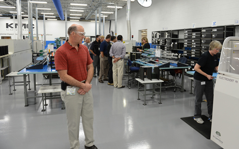Todd Thiele inspects a production process at KMC headquarters during the   In Touch 2012 dealer conference.  KMC's Deb Pederson feeds the wave-flow solder machine.